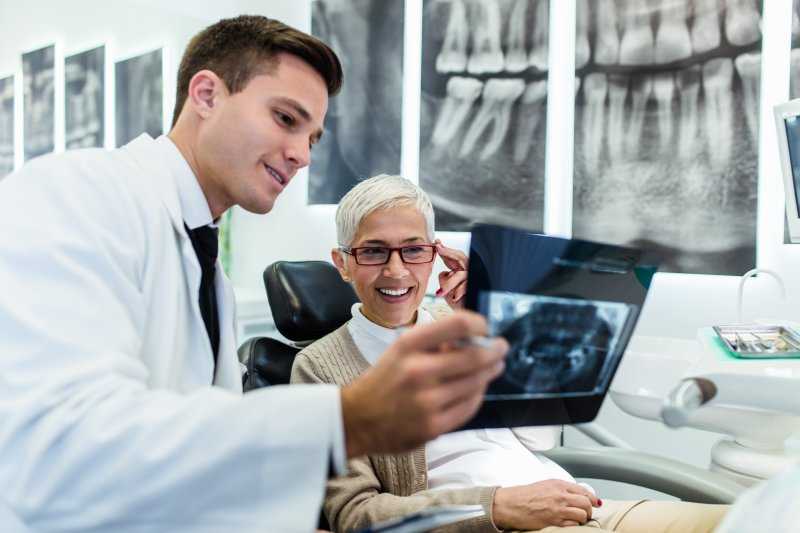 A woman looking at an X-ray with a dentist.