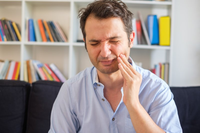 Man with gum disease on couch rubbing jaw