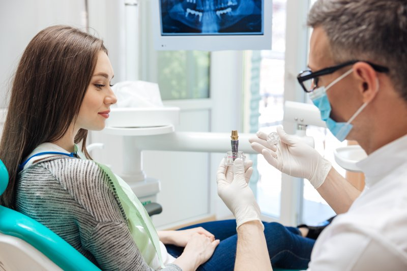Dentist with glasses showing dental implant to female patient